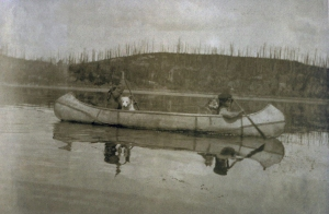 Ojibwe children with dogs in canoe